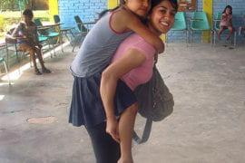 Marym Mohammady gives a piggyback ride to an orphan in Nuevo Paraiso