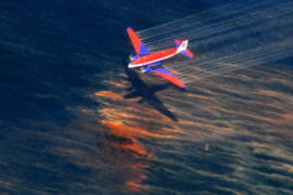 A fixed-wing aircraft releases dispersant over the oil spill