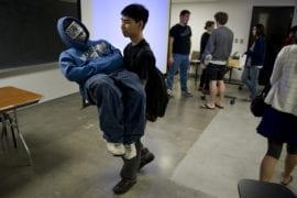 Studio art senior Joseph Chen carries his doppelganger out of class