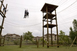 The students move in a group along one section of the rope course