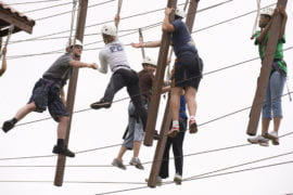 A team crossing the rope course