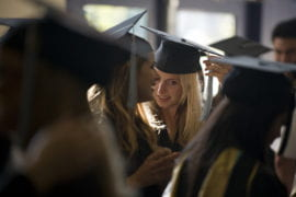 A student happily awaits her turn at commencement