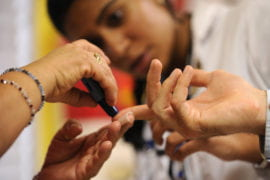 Medical students help a patient practice pricking a finger as part of blood sugar test.