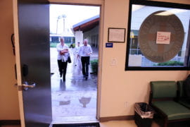 Dodging rain drops, UC Irvine health sciences students arrive to start their day at the clinic