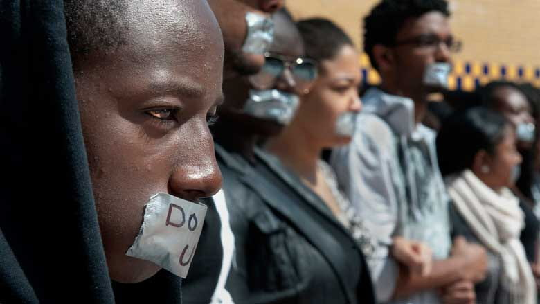 "Protesters wear duct tape over their mouths with ""Do UC us?"" written on top"