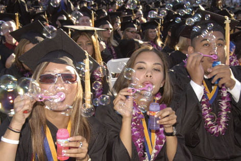 Students blowing bubbles during Commencement