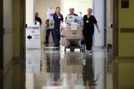 Medical staff move patient into new hospital