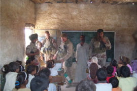U.S. military personnel help distribute school supplies
