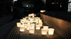 students place candles at the stage of UC Irvine Student Center