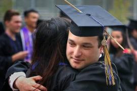 Drama grad Avi Wilk hugs a fellow graduate