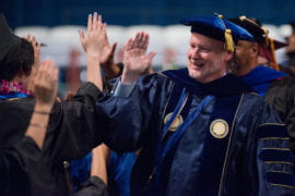 Chancellor Howard Gillman high fives newly-minted grads
