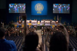 Family and friends cheer as social sciences graduates enter the Bren Events Center for commencement