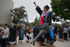 Social policy & public service grad Anthony Pham poses for a picture atop the anteater statue