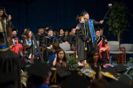 A grad utilizes a selfie stick during the School of Social Sciences commencement.