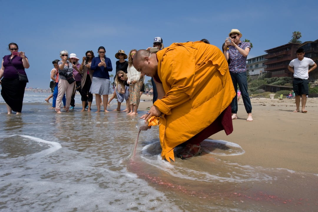 At Corona del Mar State Beach on Wednesday, a Tibetan monk releases into the ocean sand from a mandala created at UCI