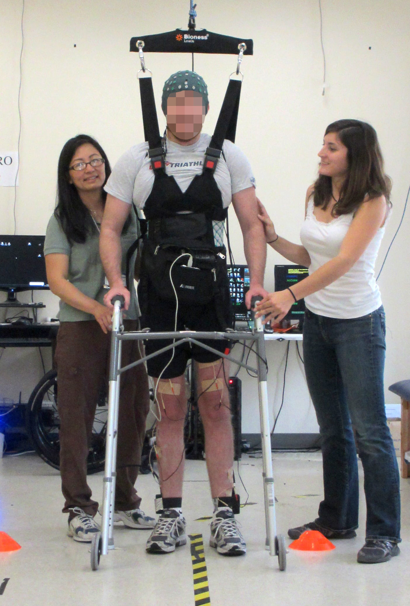 A man whose legs had been paralyzed for five years walks along a 12-foot course using UCI-developed technology that lets the brain bypass the spinal cord to send messages to the legs. Courtesy of UCI's Brain Computer Interface Lab