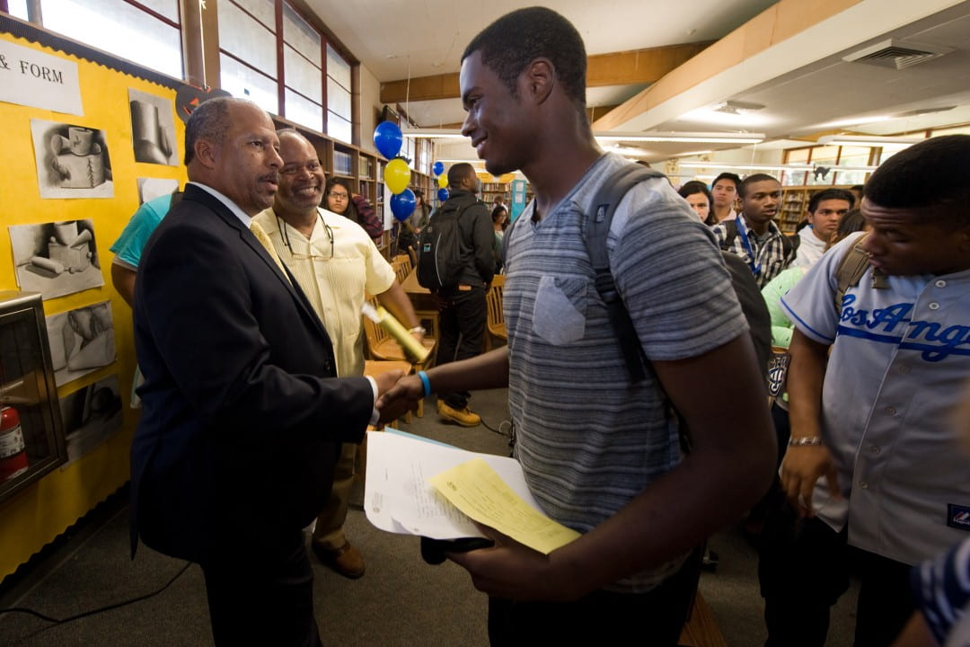 Thomas Parham, vice chancellor for student affairs, visits with a student from Manuel Domingez High School in Compton during last year's Achieve UC event.  Steve Zylius/UCI