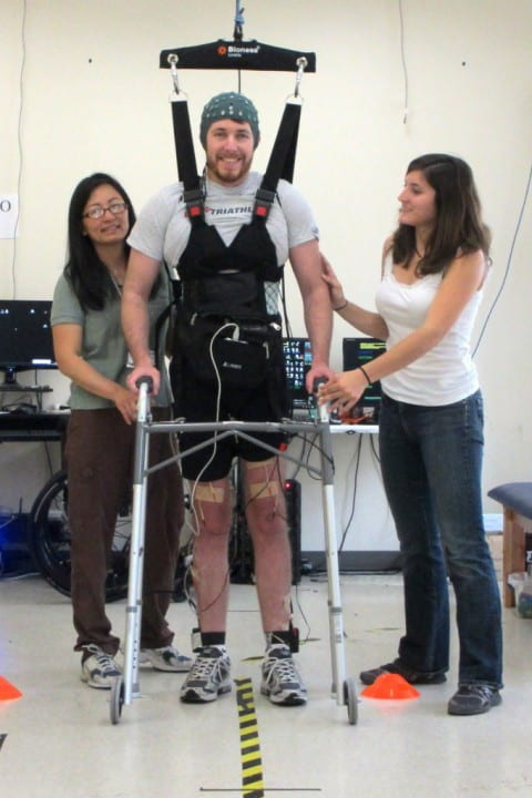 UCI's Cathy Chou (left) and Christine King help Adam Fritz prepare to take his first steps since injuring his spinal cord seven years ago. Brain Computer Interface Lab / UCI