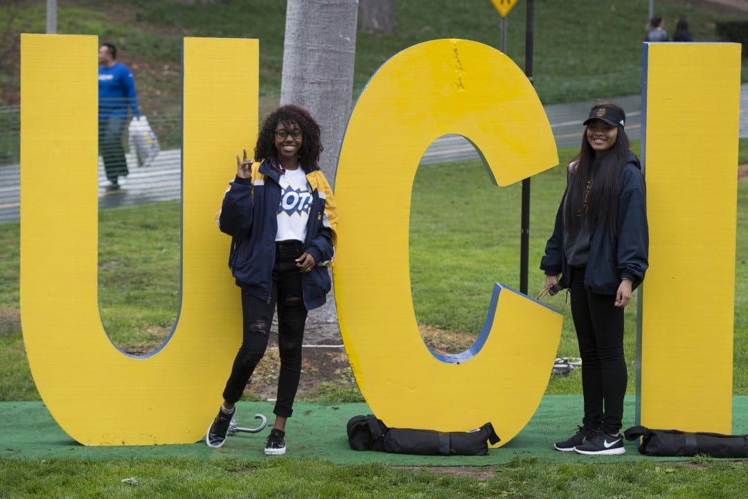 Freshman Brenyanna Harris-Hill (left), a psychology & social behavior major, and freshman Kayla Tanks, a business econ major, pose for a photo at the 2016 homecoming festival in Aldrich Park.  Steve Zylius / UCI