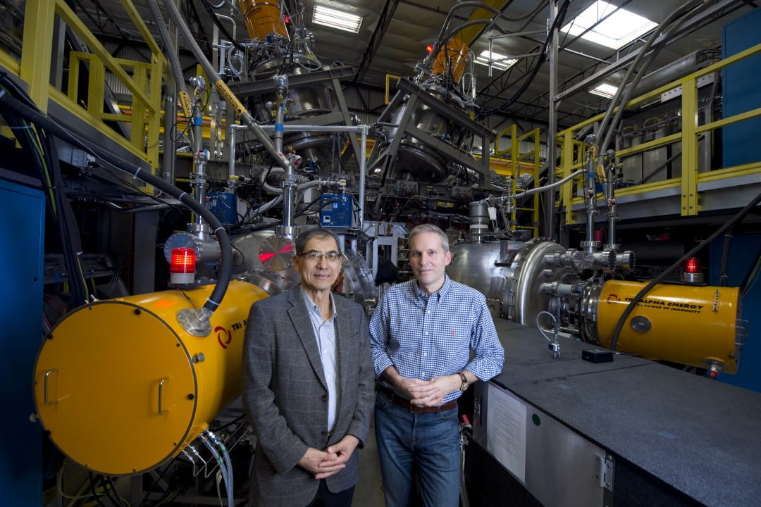 Tri Alpha Energy Chief Science Officer Toshiki Tajima (left), a UCI professor and alumnus, and TAE Chief Technology Officer Michl Binderbauer, also a UCI alumnus, are dwarfed by their fusion reactor prototype.  Steve Zylius / UCI
