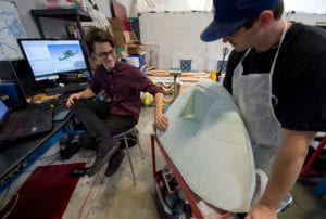 Guerrero (left) admires the handiwork of mechanical engineering major Devin Pozas, who has been preparing the 3-D printed nose cone for use in the molding of the fuselage. Steve Zylius / UCI