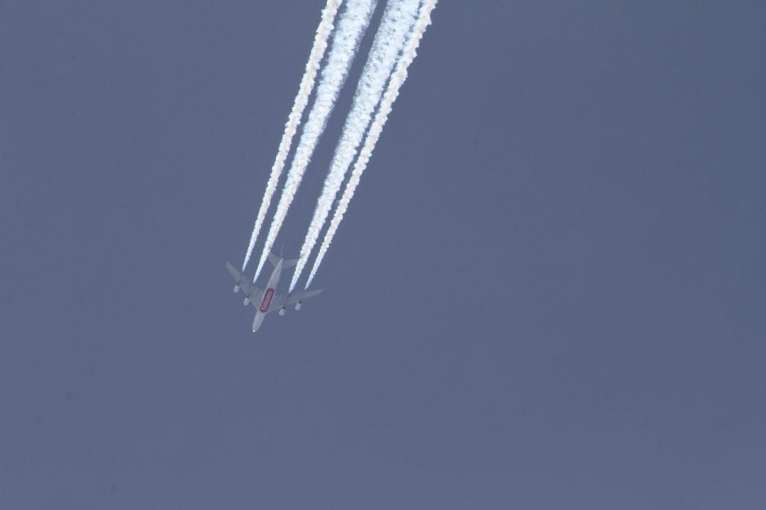 A commercial airliner produces a condensation trail