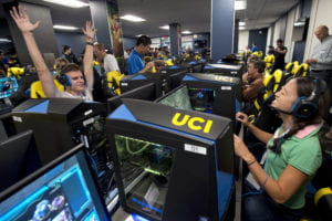 Newlyweds Ben Kempenich, an MBA alum, and Jen Jen Chen, a UCI assistant clinical professor of pediatric pulmonology, battle with each other at the opening of UCI's eSports arena. Steve Zylius / UCI