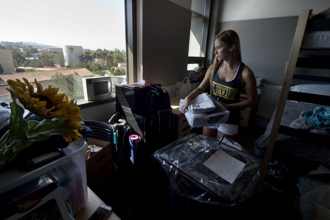 Kayte Long peruses the high-rise views from Mesa Court Towers, which include the newly painted anteater mascot on the water tank and the athletic fields.    Steve Zylius / UCI