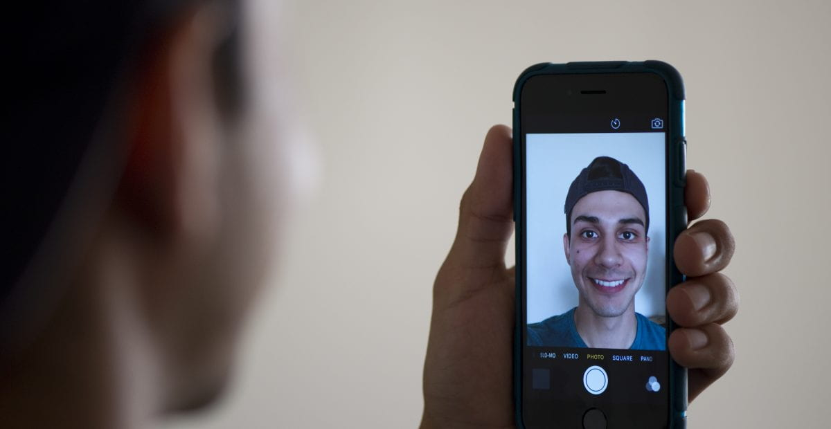"""For a recent """"positive computing"""" study by informatics researchers at UCI, subjects were asked to smile and snap a selfie with their smartphone every day for three weeks.  Steve Zylius / UCI"""