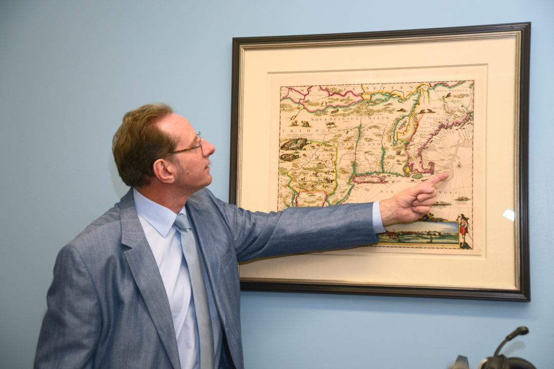Humanities Dean Georges Van Den Abbeele shows off 17th-century Dutch mapmaker Justus Danckerts' rendering of early New England, which features drawings of local animals, forts and detailed insets.  Courtesy of the UCI School of Humanities