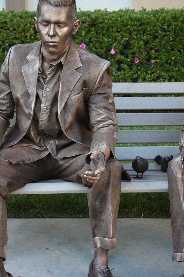 Joshua Romero, M.F.A. '17 poses as a bronze statue