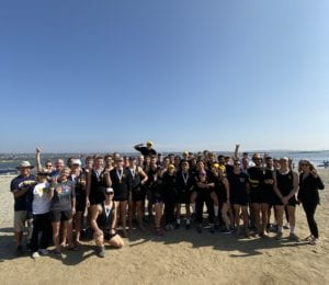 large group of people standing on the beach