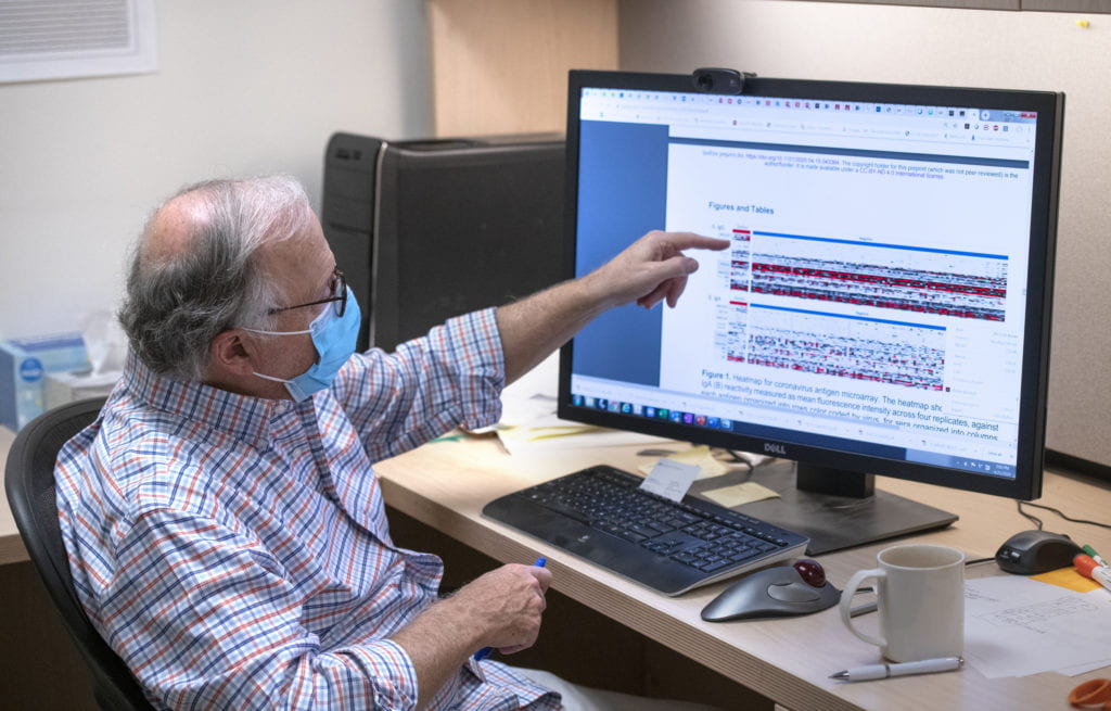 Phillip Felgner explains antibody presence, detailed in red among various diseases, and notes the absence of coronavirus antibodies, in top row of computer screen image.