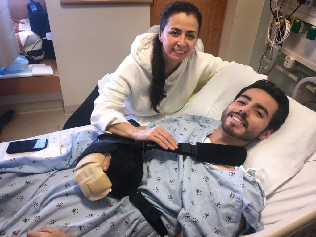 Christian Lopez (in hospital bed) and his mother, Sandra, are all smiles on the day of his discharge from UCI Medical Center.