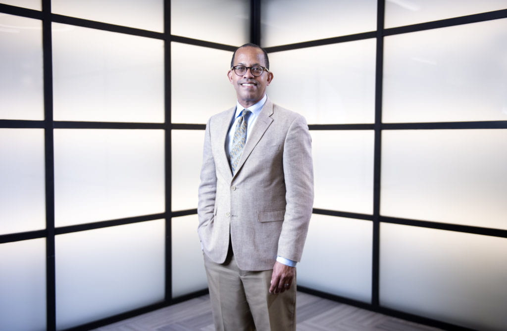 Douglas M Haynes stand in front of two walls made up of lit up panels. He is smiling with his right hand in his pocket