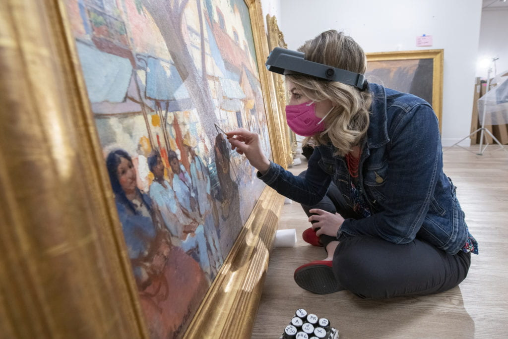 Morgan Wylder, an assistant conservator of paintings with the Balboa Art Conservation Center, carefully swabs a painting that's being prepared for display at the Institute and Museum of California Art.