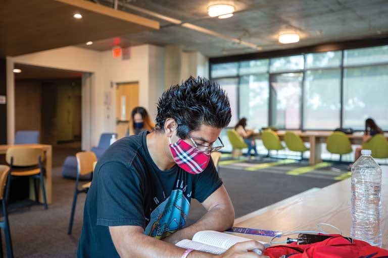 Male student wearing mask, reading book