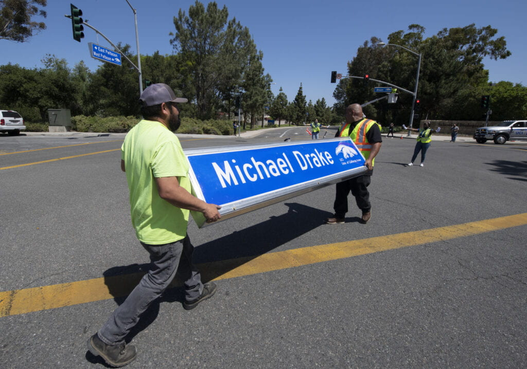 Two men carrying a street sign that says Michael Drake,