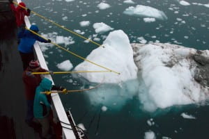 UC Irvine glaciologists aboard the MV Cape Race in August 2014 muscle away icebergs from delicate sonar equipment, lower middle, used to map remote Greenland fjords for the first time. Maria Stenzel / for UC Irvine