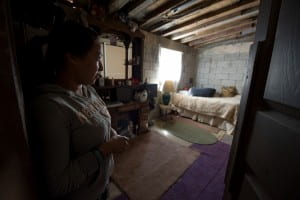 Los Laureles Canyon resident Silvia Rico Medina shows UCI FloodRISE participants her bedroom, which floods when wind-whipped rain blows in sideways through the window. The roof, made from a plastic presidential campaign sign, also leaks. Steve Zylius / UC Irvine