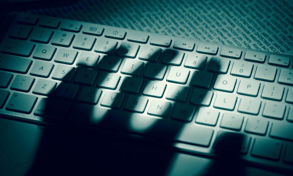 menacing shadow of a hand on a neyboard