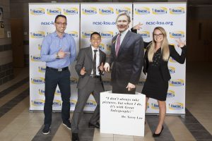 Professor Plamen Peev, Lary Zhang and Alicia jones posing with a cardboard cut out at the national collegiate sales competition