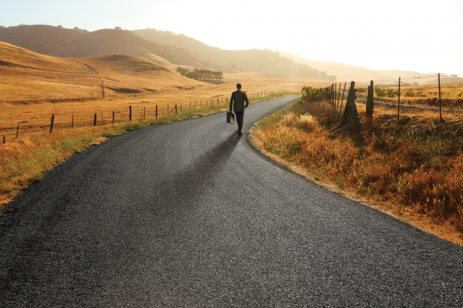 a lone man in a business suit carrying a brief case down a long and winding country road