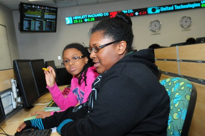 two young girls working at a bloomberg terminal in the finance lab