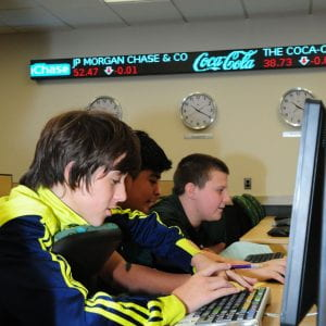 three boys working at a bloomberg terminal in the finance lab