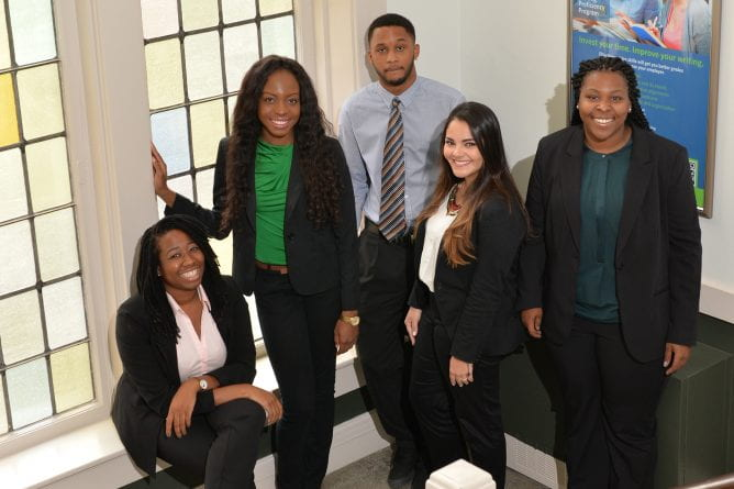 a group of student consultants wearing business attired pose in the stairway of Stephens Hall