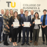 The winning team of the fall 2019 live strategy case competition poses with executives from presenting company Howard Bank