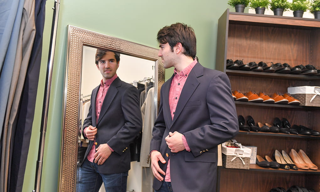 male student looks in the mirror while trying on a suit jacket