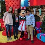 three people posing with Minney Mouse character at Disneyland