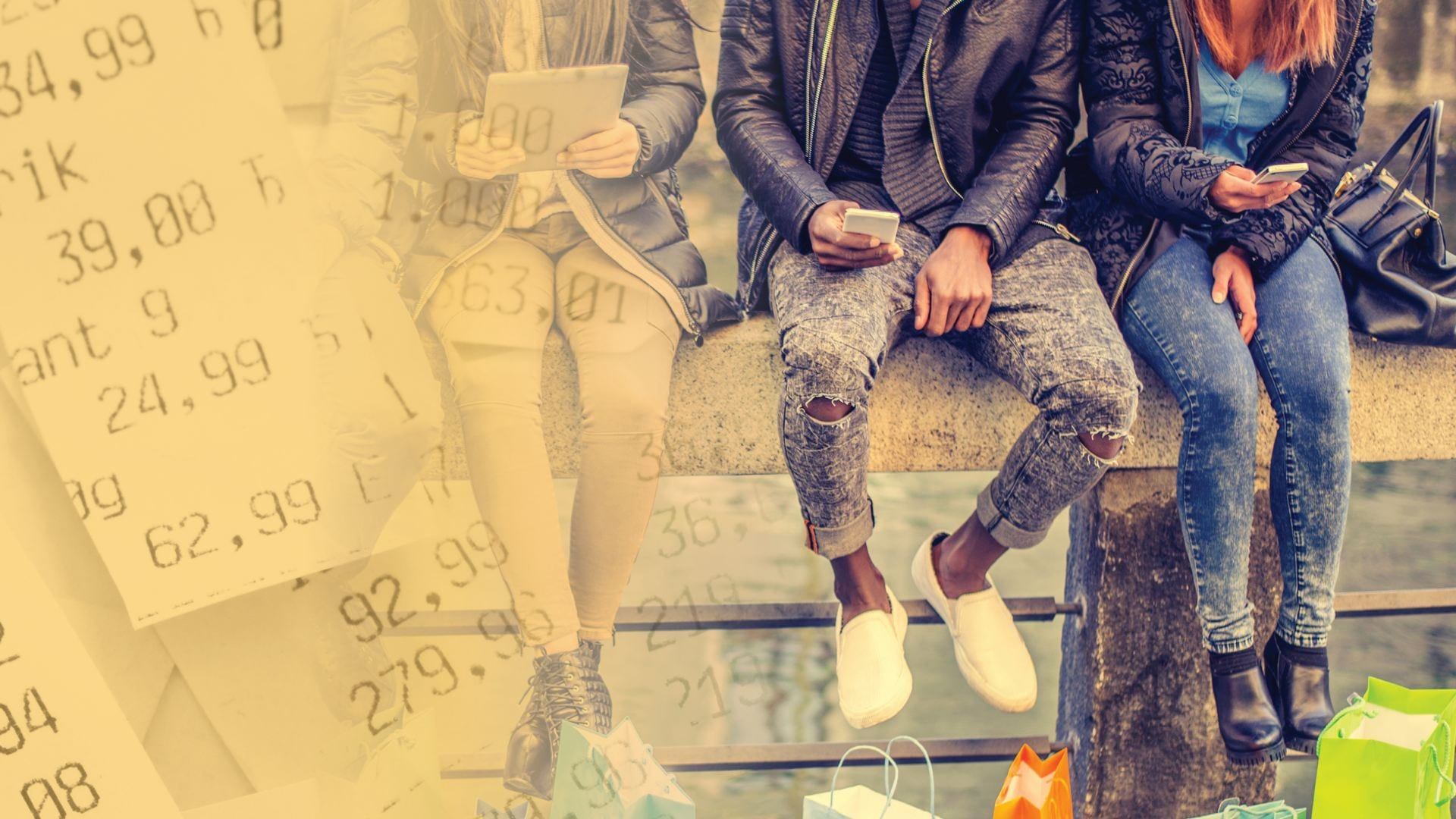 three young people sit on a wall looking at their mobile phones with shopping bags at their feet